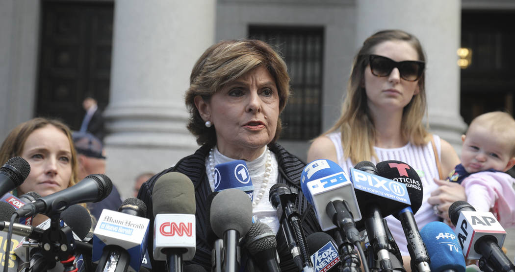 Attorney Gloria Allred, center, flanked by two of her clients, speaks during a news conference ...