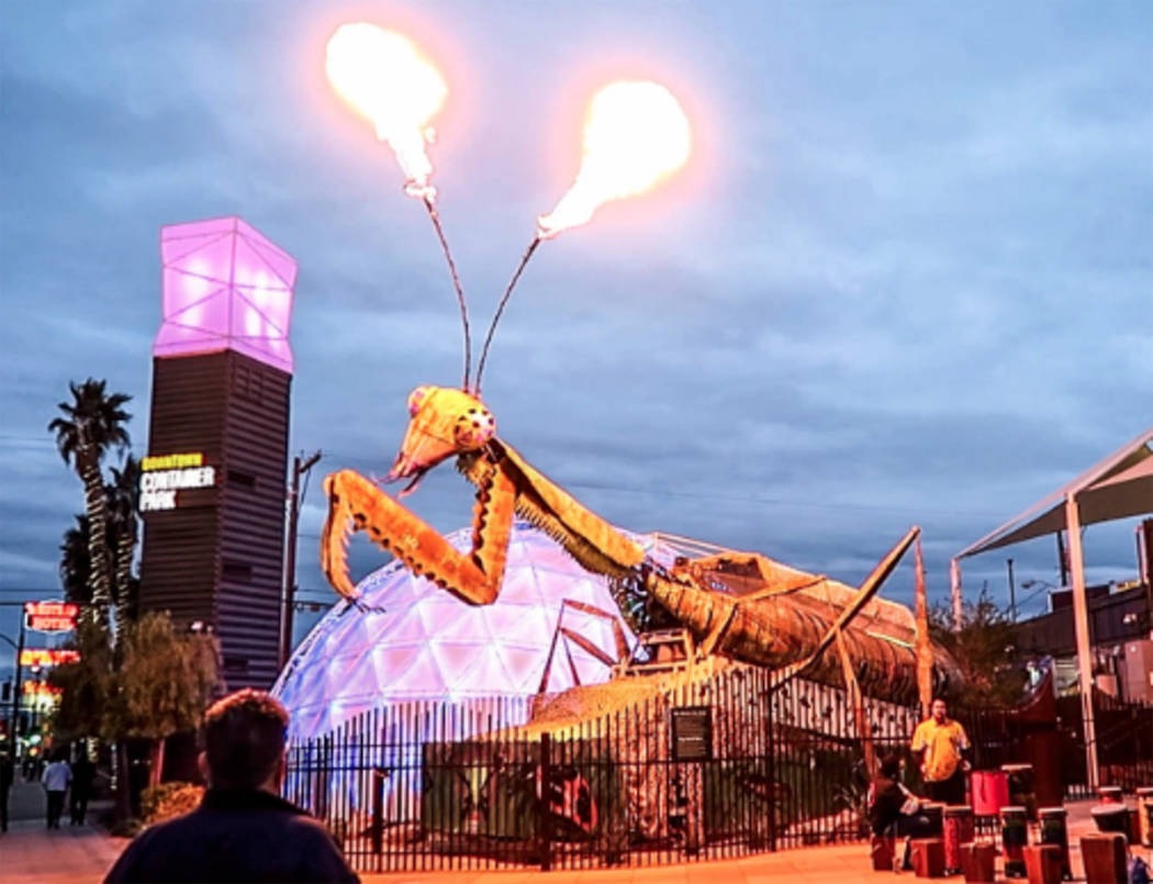 The mantis at Container Park shoots fire as running pass by during the Rock-n-Roll Marathon on ...