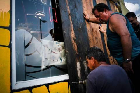 Men board up a shop's windows ahead of the arrival of Hurricane Dorian in Boqueron, Puerto Rico ...