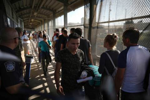 In a Aug. 2, 2019, file photo, migrants return to Mexico as other migrants line up on their way ...