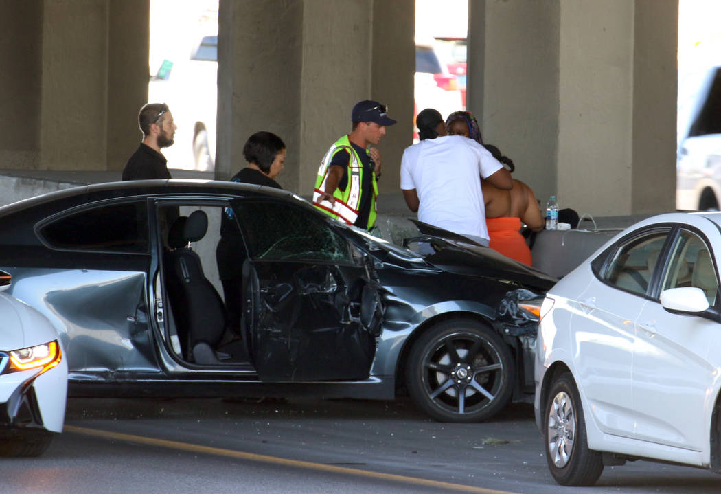 A Las Vegas firefighter assists an injured driver at the scene of multi-vehicle crash at US Hig ...