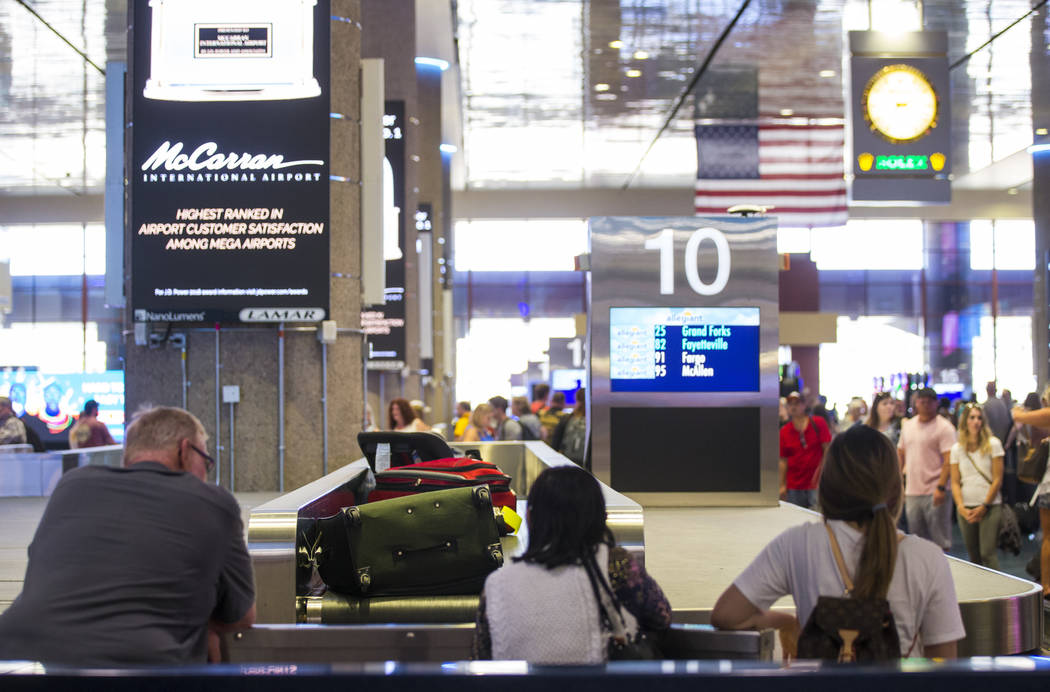 Passengers wait for luggage at the baggage claim area at McCarran International Airport ahead o ...