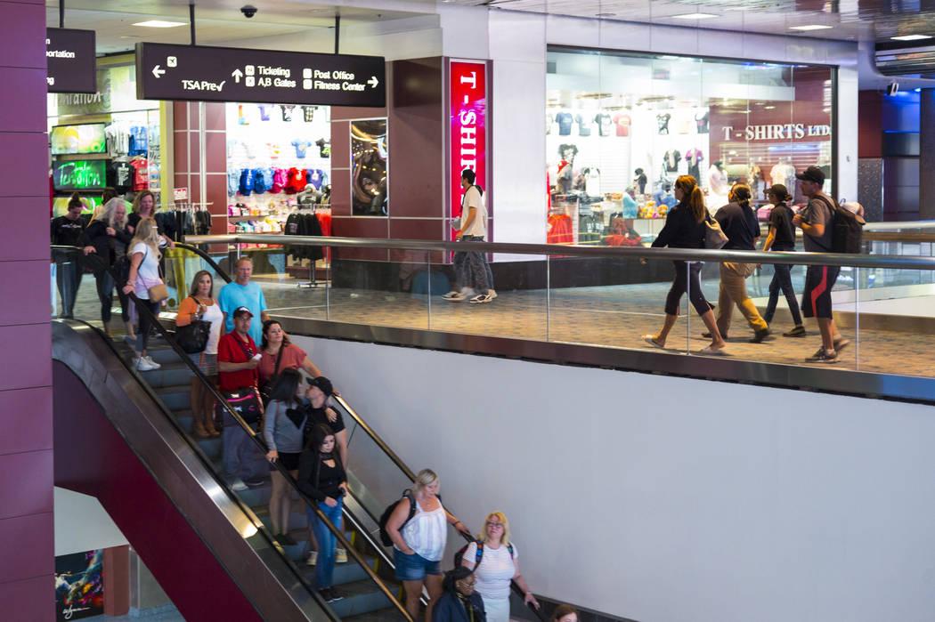 Passengers make their way to baggage claim and transportation at McCarran International Airport ...