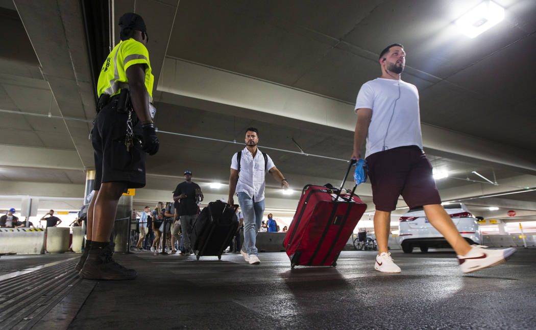 Passengers using rideshare services walk to their respective vehicles after arriving at McCarra ...