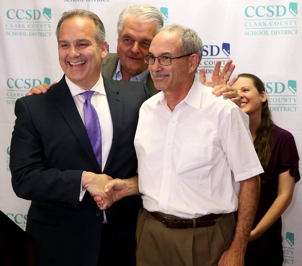 Gov. Steve Sisolak, center, prods Clark County School District Superintendent Jesus Jara, left, ...