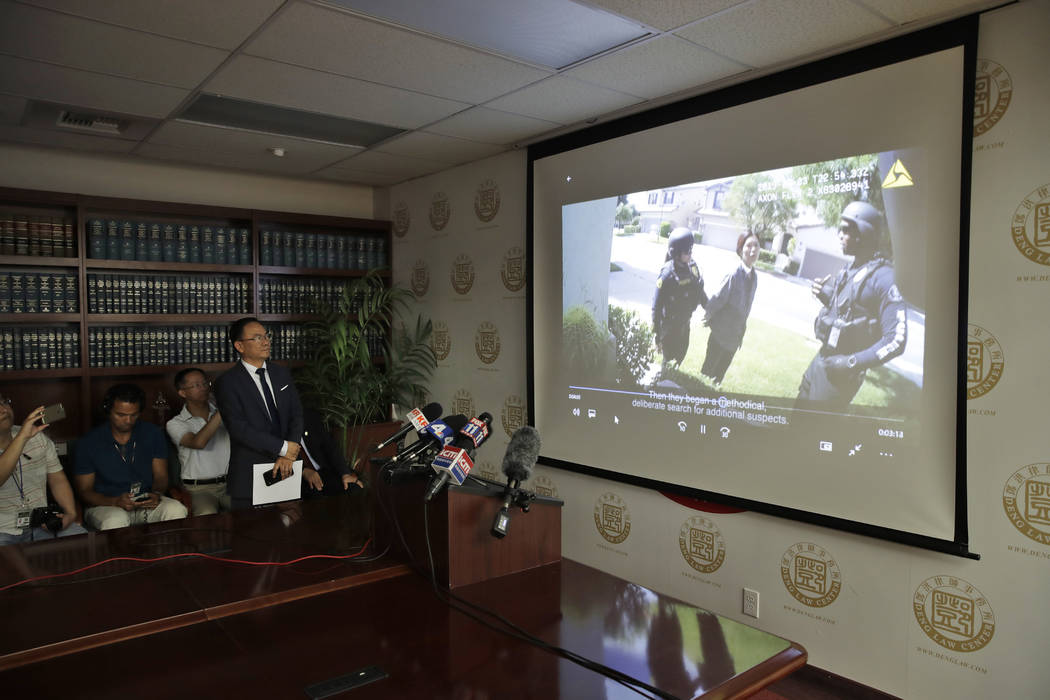 Dr. Henry Lee, left, a forensic scientist, watches a body cam video Wednesday, Aug. 28, 2019, i ...