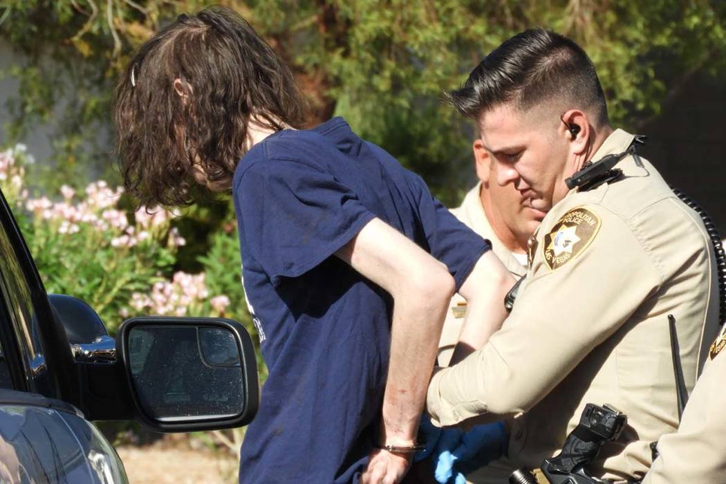 Las Vegas police take a suspect into custody as they investigate a stabbing in the 6500 block o ...