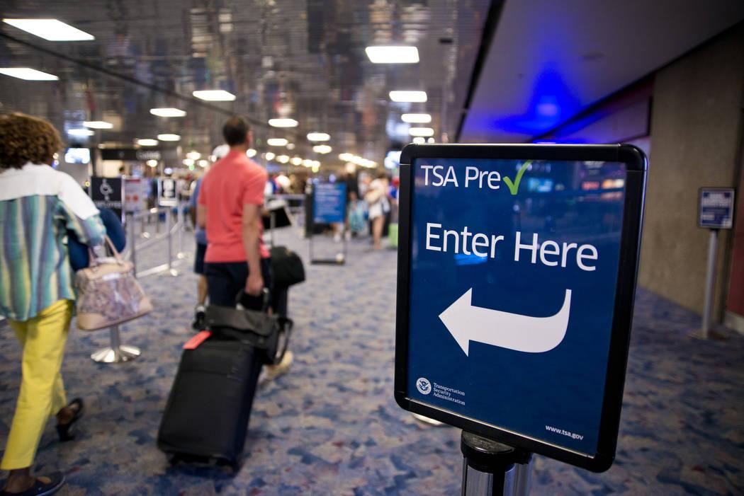 Passengers walk toward the TSA PreCheck security line at McCarran International Airport in Las ...