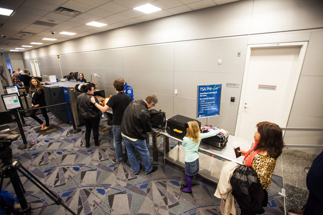 Passengers move through pre-check lane at the Terminal 3 TSA checkpoint at McCarran Internation ...