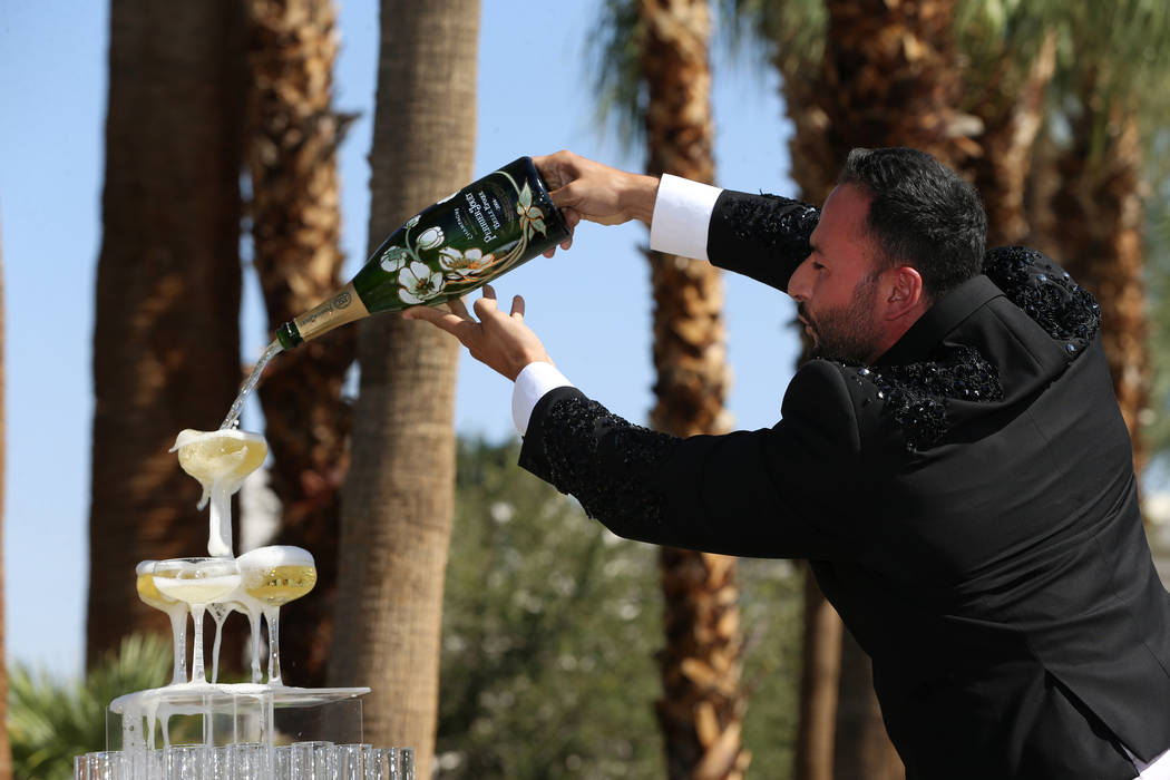 Monsieur Romeo, cast member for Blanc de Blanc, pours champagne during a rebranding event for S ...