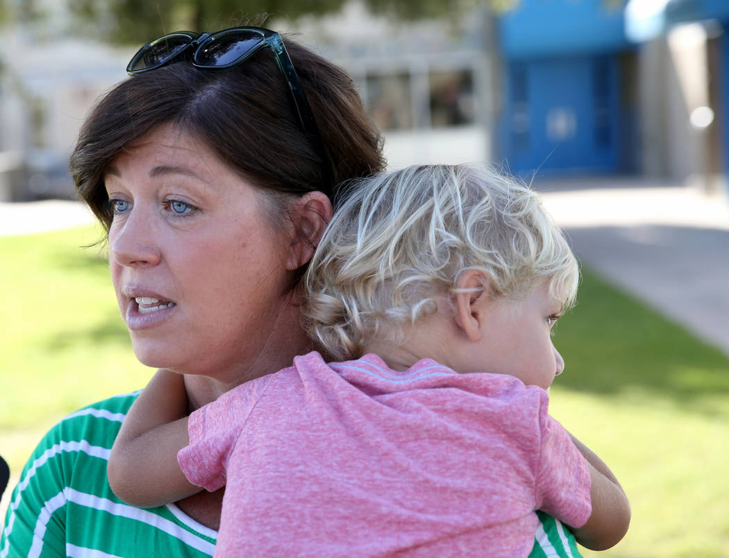 Parent Shellie Tingey talks to a reporter while holding her child Stafford Tingey, 3, at Helen ...