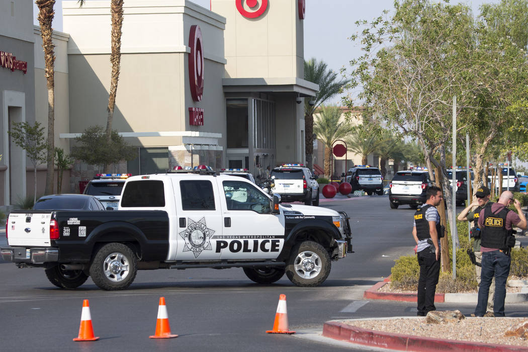 Police investigate an officer-involved shooting at a shopping complex near Blue Diamond Road an ...