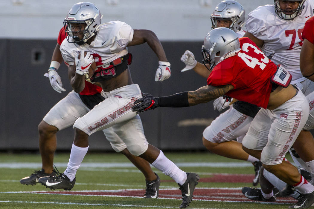 Charles Williams (8) blasts through a hole past defenders including Malakai Salu (43) during th ...
