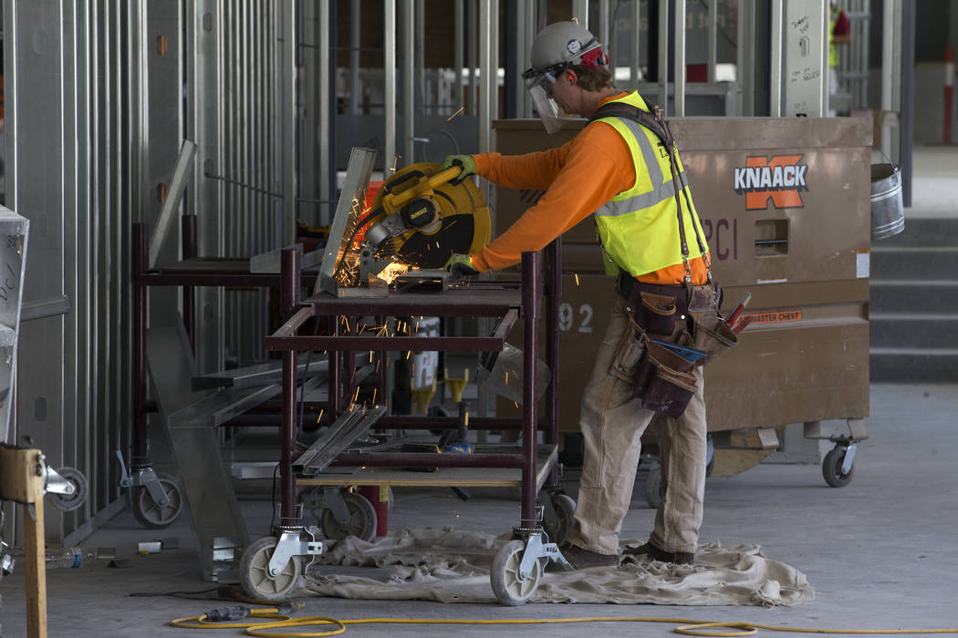 A worker cuts a piece of metal at the Raiders Allegiant Stadium construction site in Las Vegas, ...