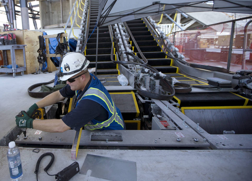 Escalator foreman Cory Johnston works on newly installed escalators at the Raiders Allegiant St ...