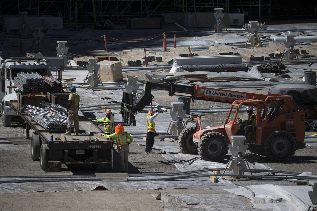 Workers move equipment from the floor level of the Raiders Allegiant Stadium construction site ...