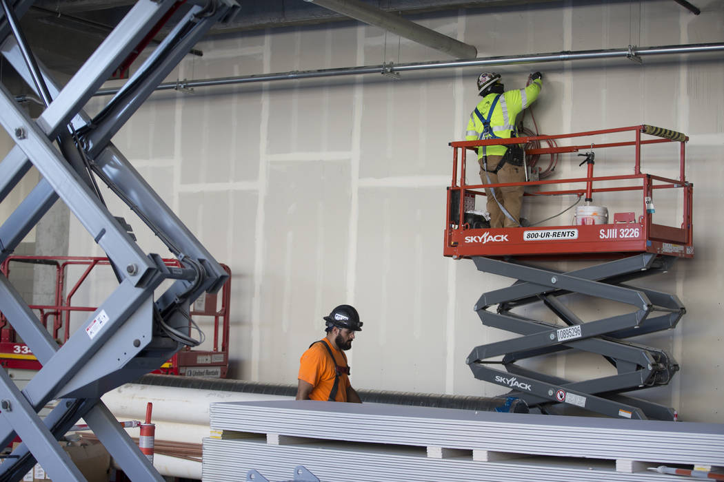 A worker, right, patches a wall at the Raiders Allegiant Stadium construction site in Las Vegas ...