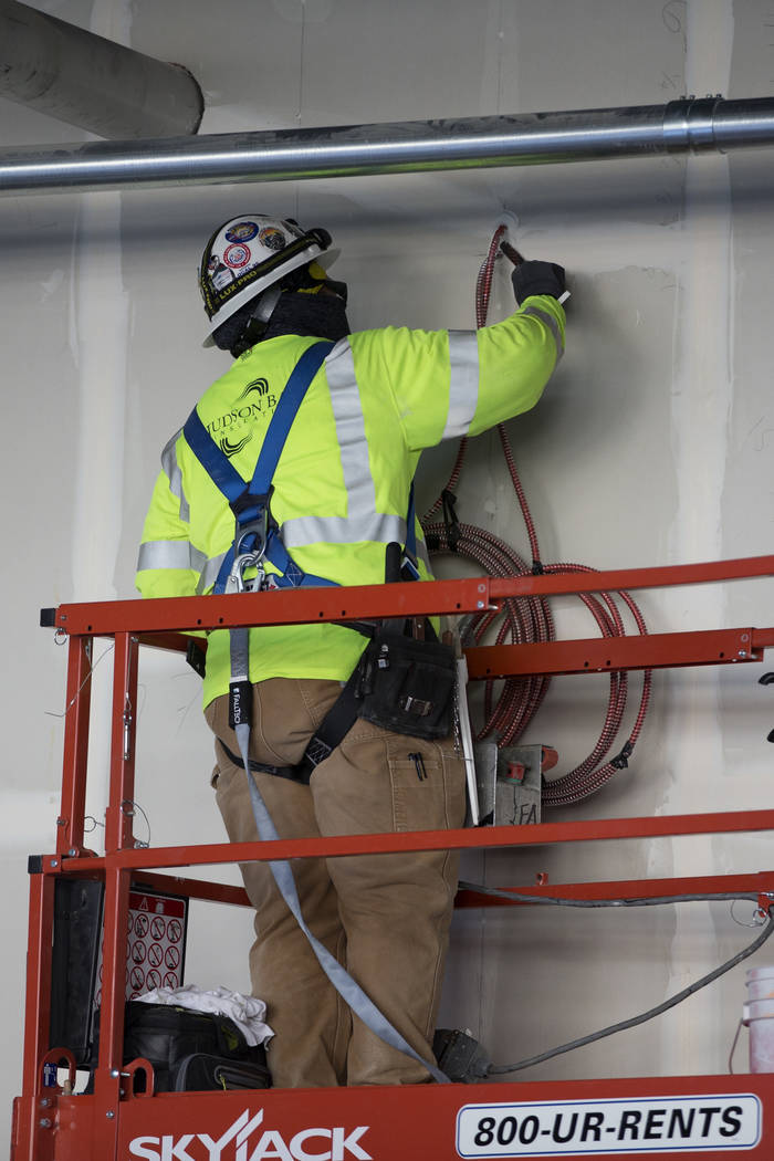 A worker patches a wall at the Raiders Allegiant Stadium construction site in Las Vegas, Wednes ...