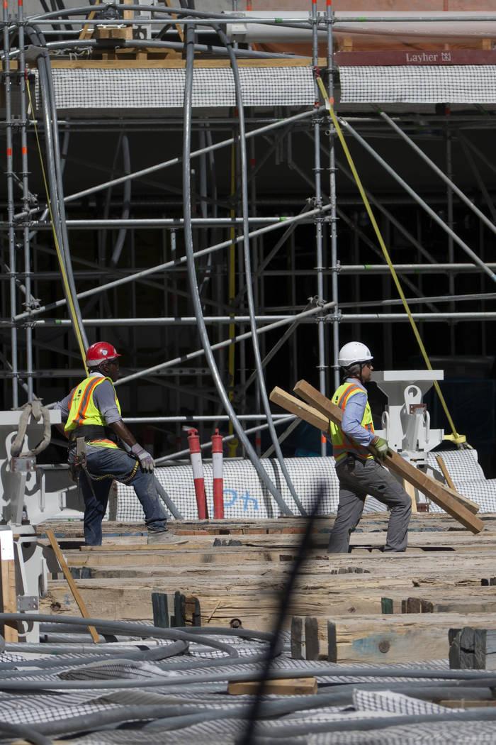 Workers walk on the floor level of the Raiders Allegiant Stadium construction site in Las Vegas ...
