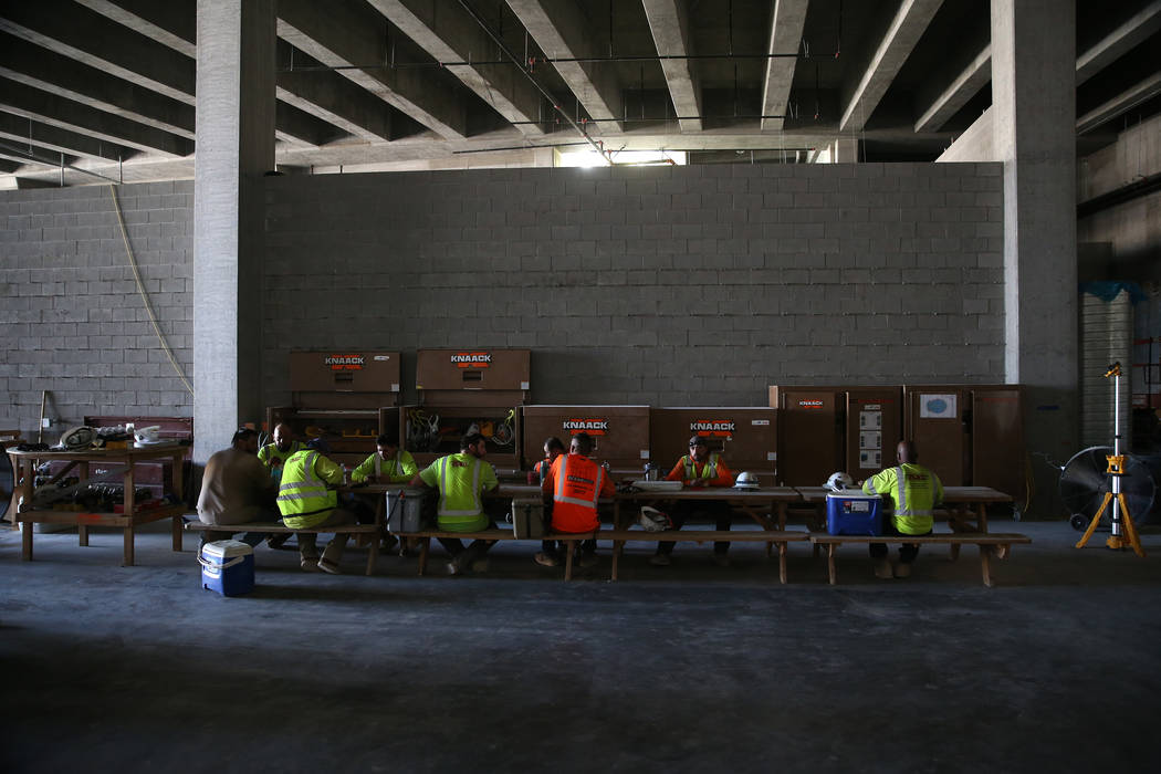 Workers sit for lunch at the Raiders Allegiant stadium construction site in Las Vegas, Wednesda ...