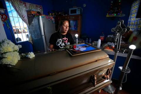 Vanessa Galindo Blas, 32, places a rose on a photograph atop the coffin of her late husband Eri ...