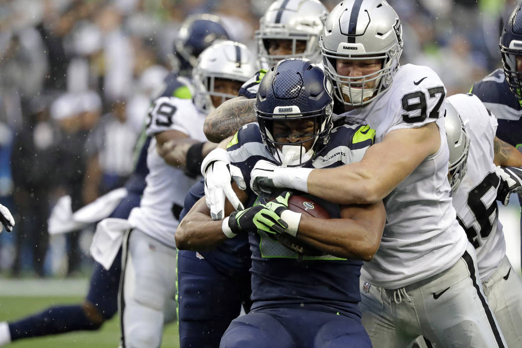 Seattle Seahawks running back C.J. Prosise, center, is tackled by Oakland Raiders defensive end ...