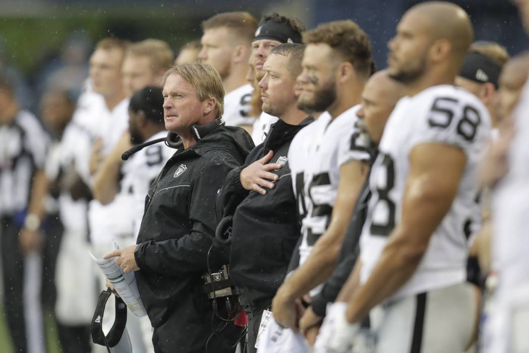 Oakland Raiders head coach Jon Gruden, center, stands with his players during the singing of th ...