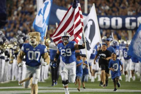 BYU offensive lineman Tristen Hoge (69) carries a U.S. flag onto the field before the team's NC ...