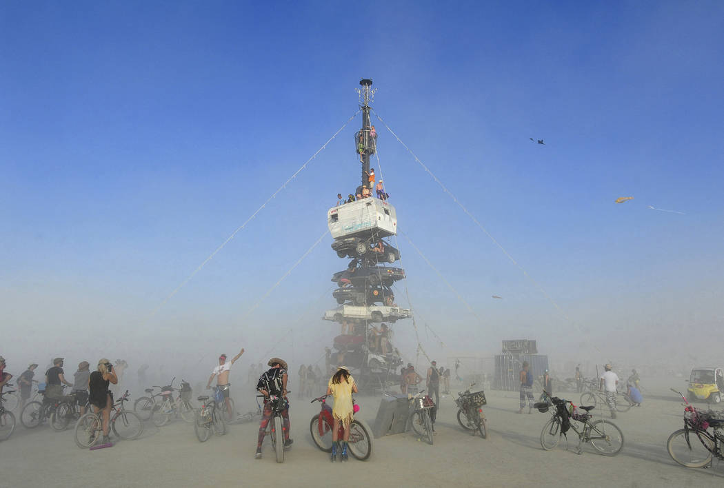 """Burners"" surrounded by playa dust climb onto an art installation titled ""Night of the Climb"" a ..."