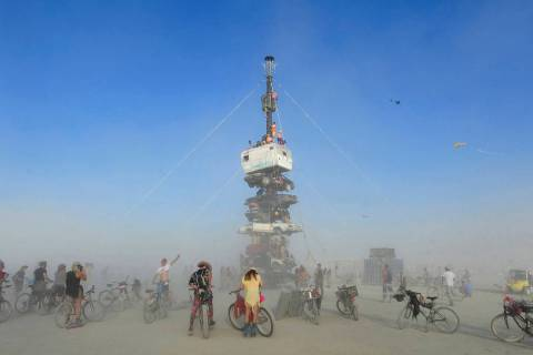 """""""Burners"""" surrounded by playa dust climb onto an art installation titled """"Night of the Climb"""" a ..."""