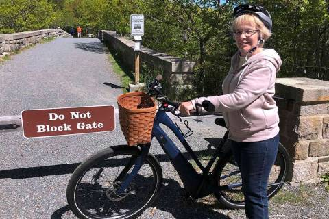 In a June 8, 2019, file photo, Janice Goodwin stands by her electric-assist bicycle at a gate n ...