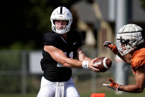 Texas quarterback Sam Ehlinger, left, and running back Jordan Whittington, right, take part in ...