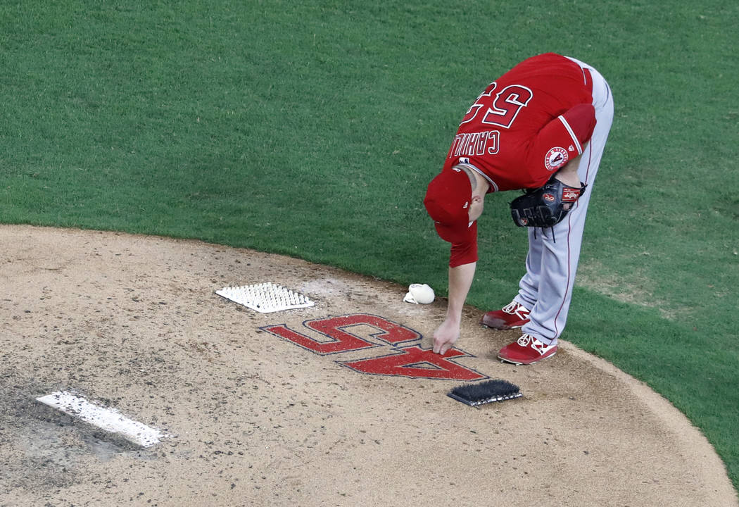 Los Angeles Angels starting pitcher Trevor Cahill (53) reaches down to touch the number 45 on t ...