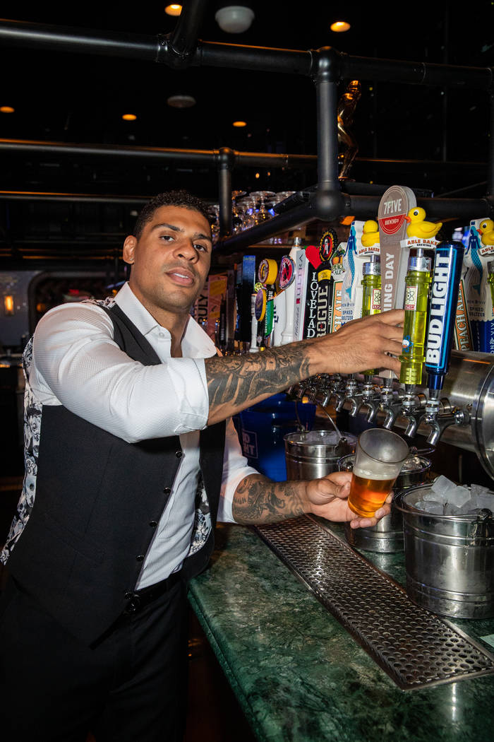 Ryan Reaves is shown tending the bar and posing for the photos at Moneyline Sports Book & Bar a ...
