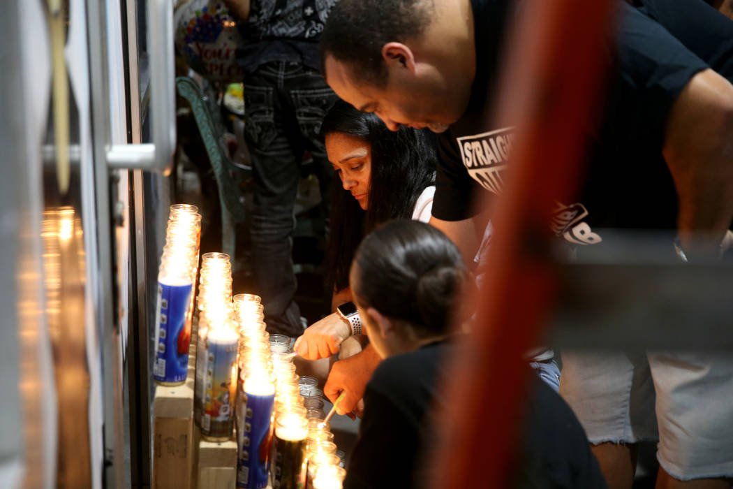Anthony Randolph, 45, his wife Yesbeth Randolph, 45, and daughter Leyla, 11, light candles duri ...
