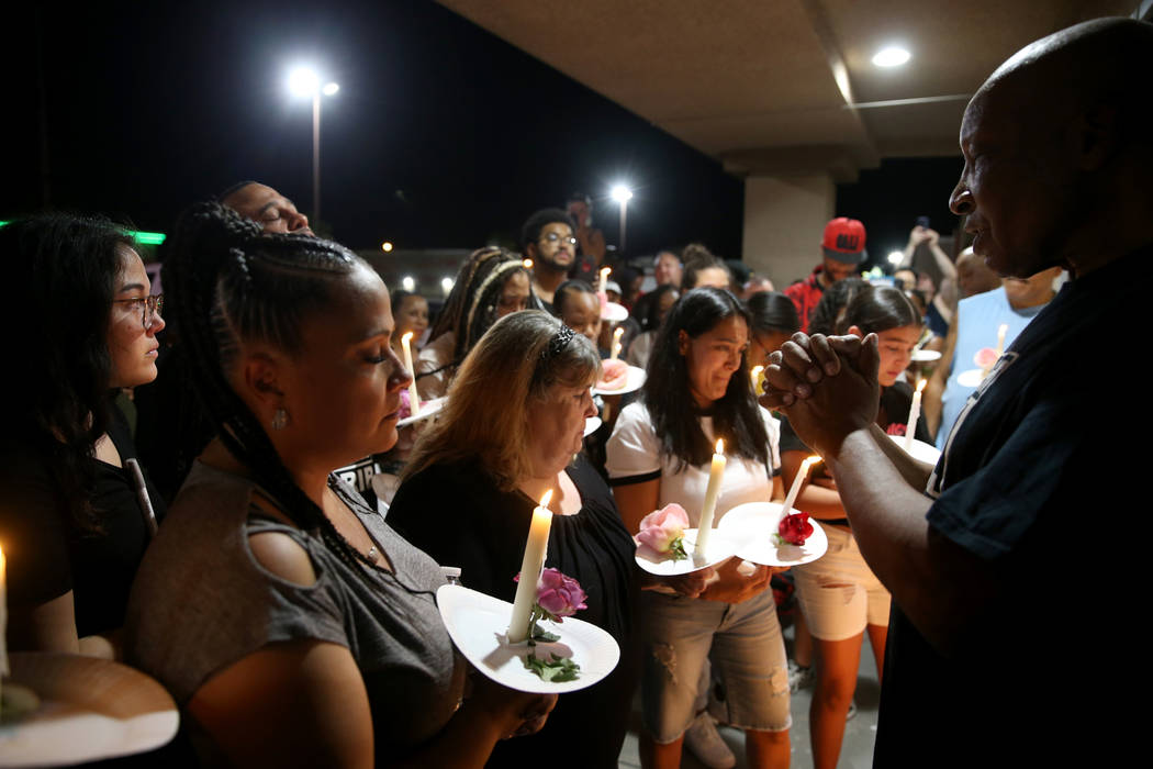 Richard Steele, right, leads a prayer for mourners, including Michelle Corrales-Lewis, left, du ...