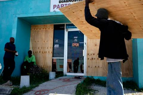 Workers board up a shop's window front as they make preparations for the arrival of Hurr ...