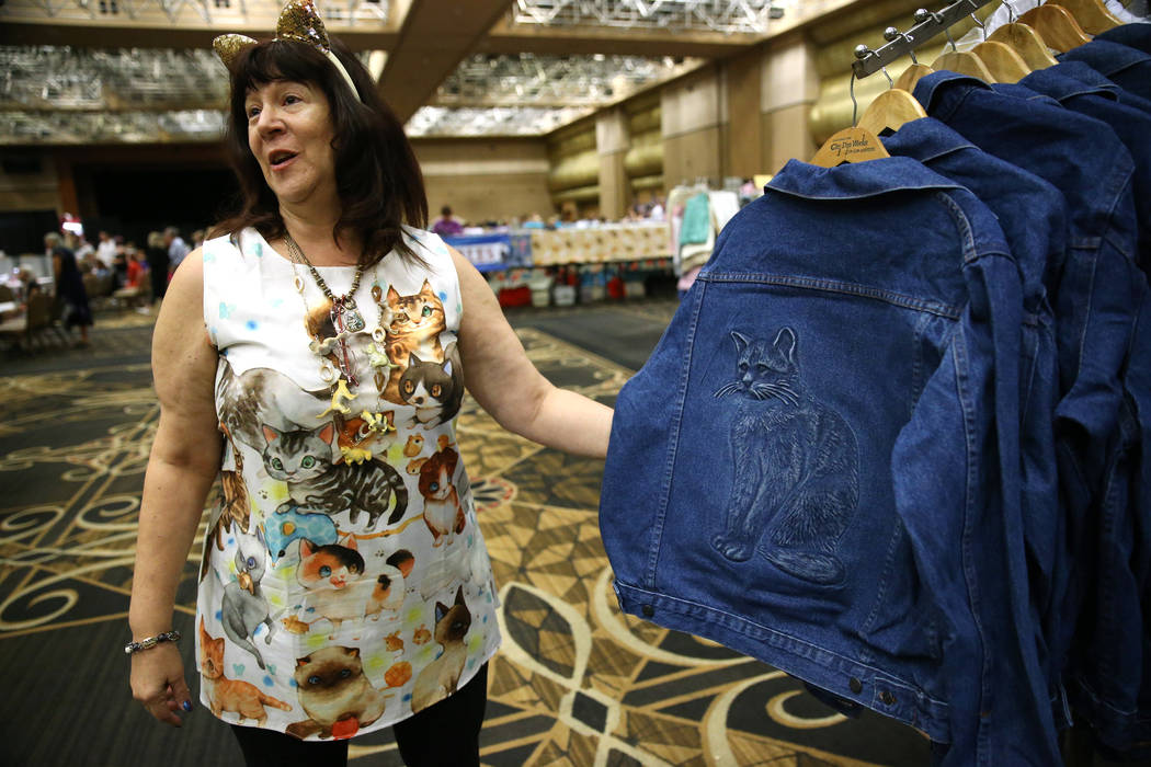 Temmie Silver, owner of Paws and Pals, shows a cat themed jacket for sale in her booth during T ...
