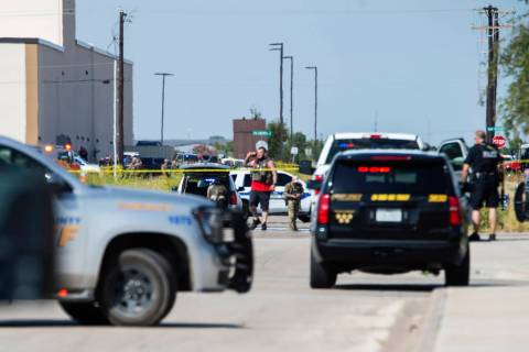 Odessa and Midland police and sheriff's deputies surround the area behind Cinergy in Odessa, Te ...