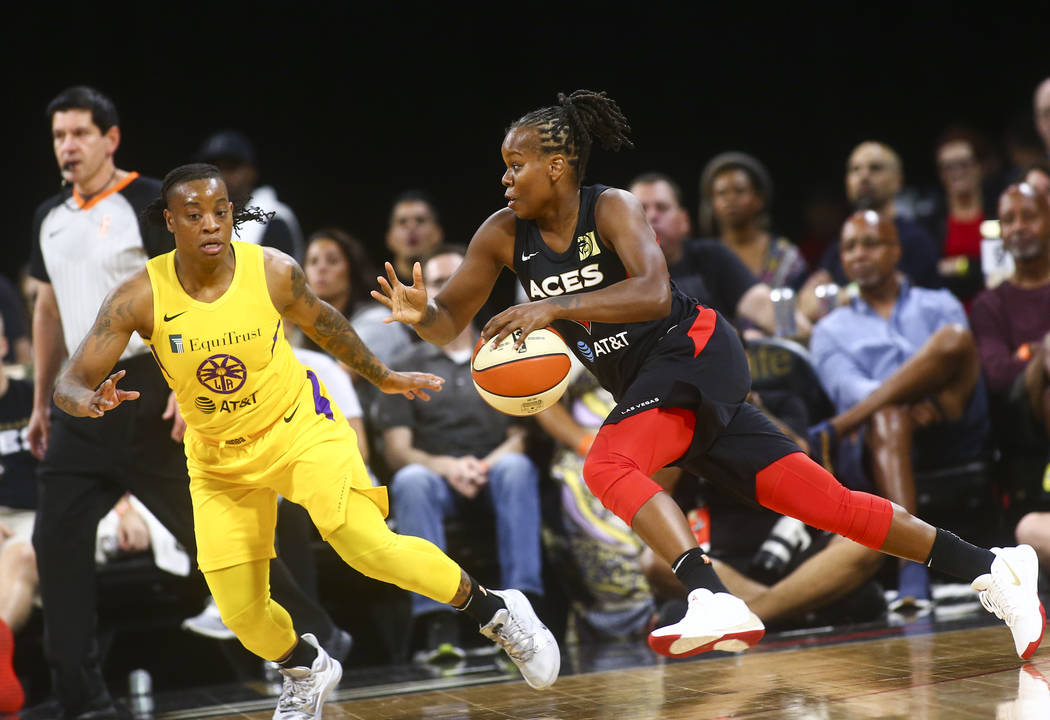 Las Vegas Aces' Epiphanny Prince, right, drives the ball against Los Angeles Sparks' Riquna Wi ...