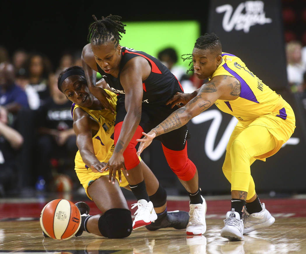 Las Vegas Aces' Epiphanny Prince battles for the ball between Los Angeles Sparks' Chiney Ogwumi ...