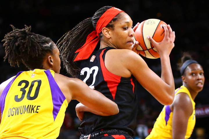 Las Vegas Aces' A'ja Wilson (22) moves the ball around Los Angeles Sparks' Nneka Ogwumike (30) ...