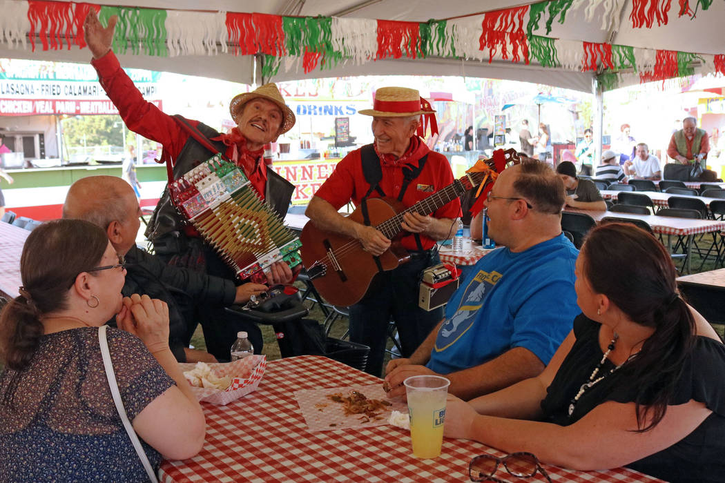 Emilio Baglioni, left, and Aldo Vallera serenade a group of people during the San Gennaro Feast ...