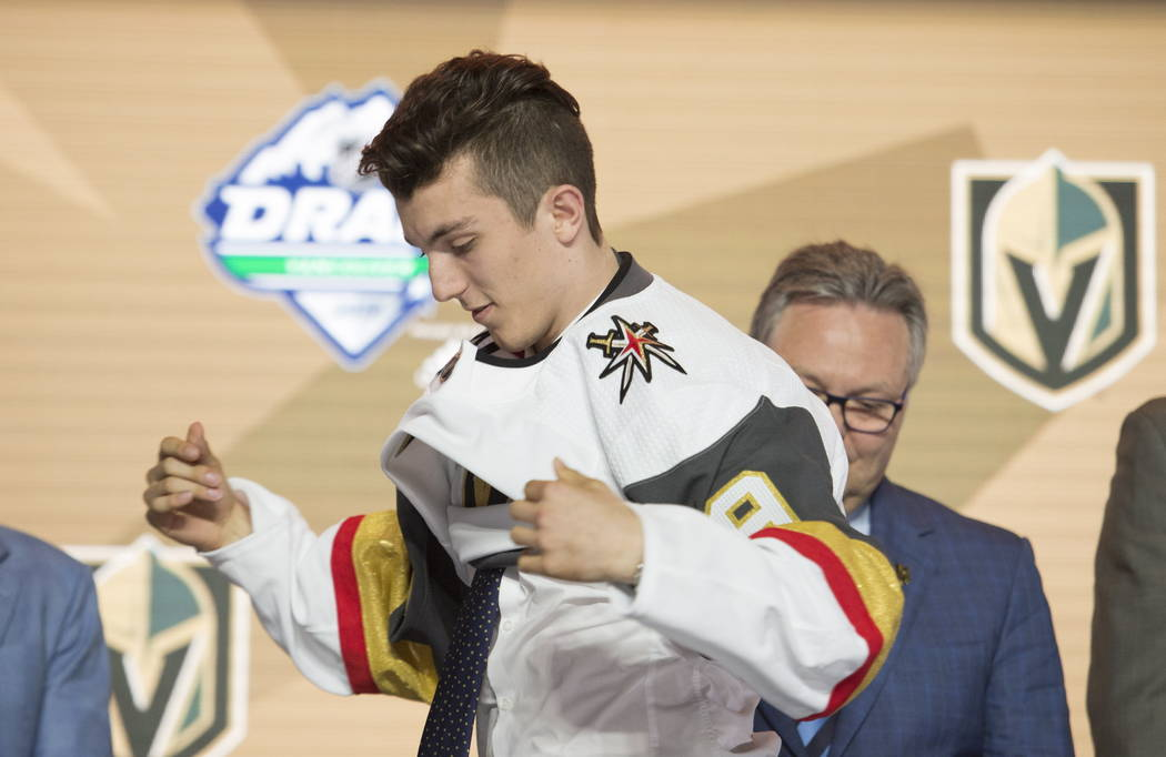 Peyton Krebs puts on a Vegas Golden Knights jersey during the first round of the NHL hockey dra ...