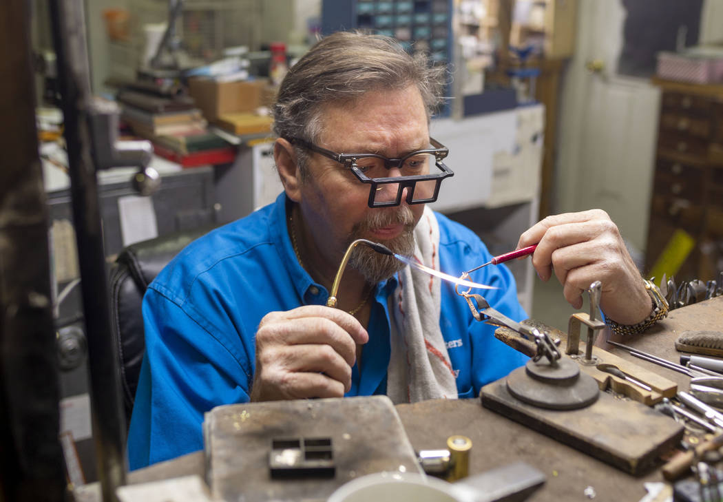 Gold Casters Jewelry owner Michael Holland prepares a wedding ring to be set in his workshop at ...