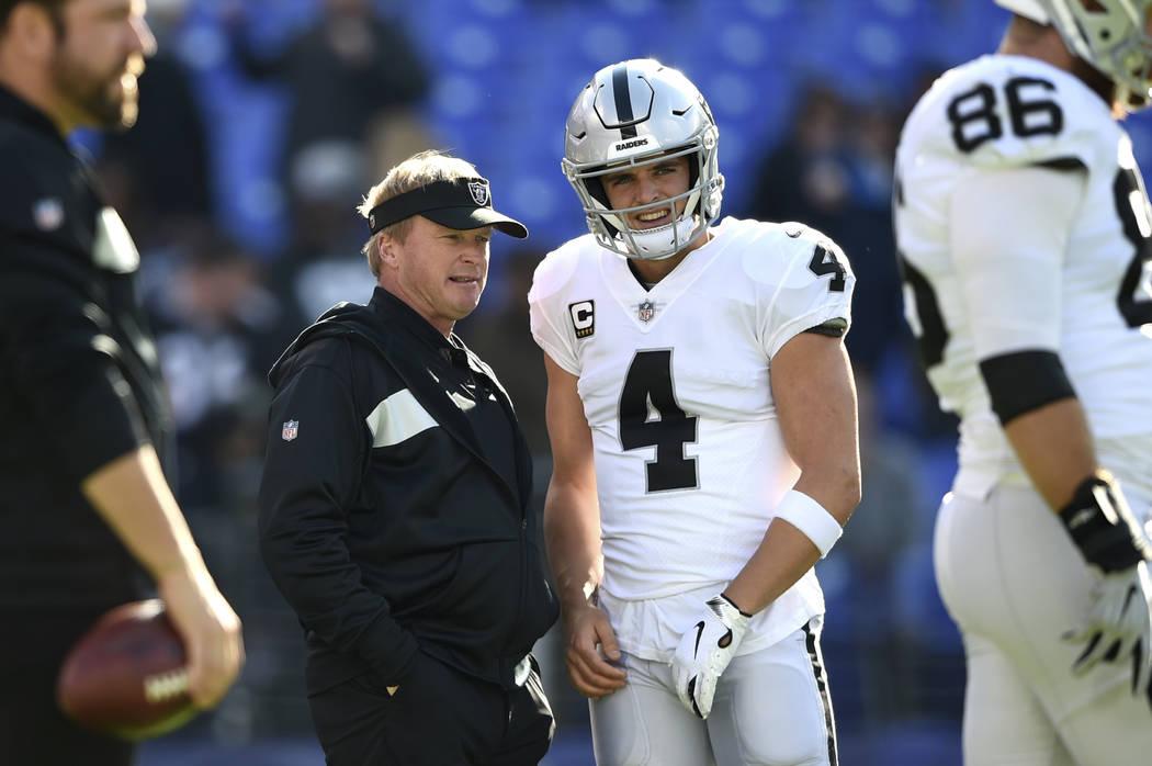 Oakland Raiders coach Jon Gruden, center left, speaks with quarterback Derek Carr before the te ...