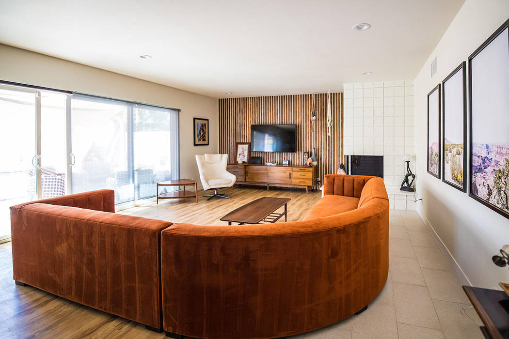 A rust colored sectional adds another retro dimension among the midcentury furniture pieces. (T ...