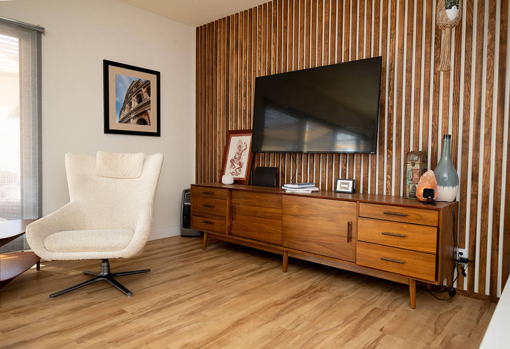 The living room features an accent wall that has strips of wood to match the 1960s vibe. (Tonya ...
