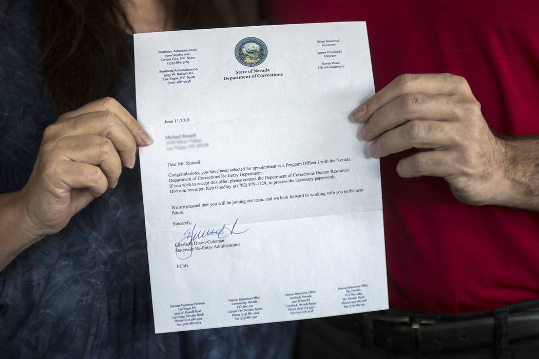 Michael Russell and his mother, Jill Drysdale, hold the letter from the Nevada Department of Co ...