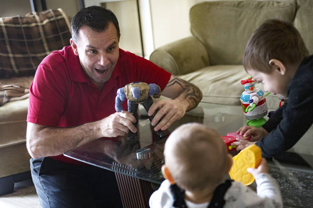 Michael Russell plays with his great-nephew Cameron Gonzales, 2, and great-niece Ava Gonzales, ...